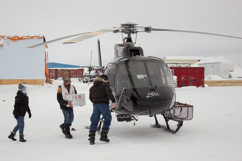 Jason Coonishish carries box of vaccines to helicopter