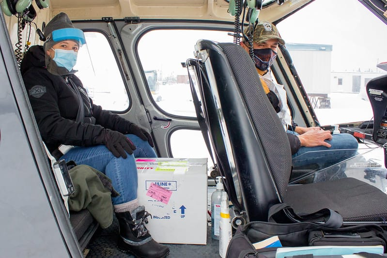 Guylaine Boula and Jason Coonishish on helicopter with box of vaccines