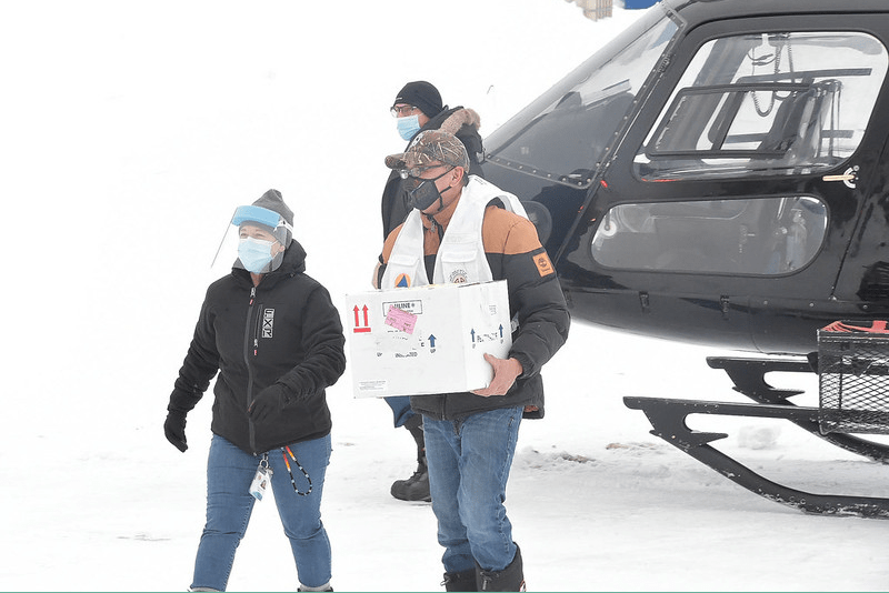 Jason Coonishish and Guylaine Boula bring box of vaccines out of helicopter