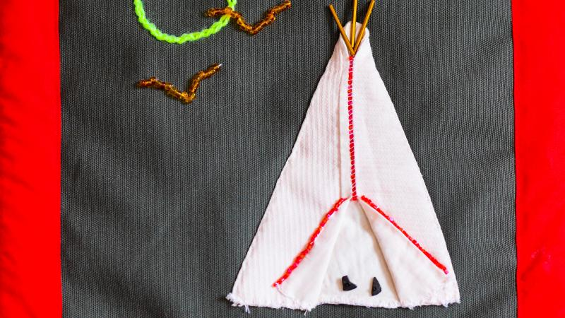 Stitching on felt material showing teepee and geese flying