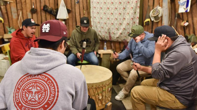 Drumming circle with one drummer shielding his ears