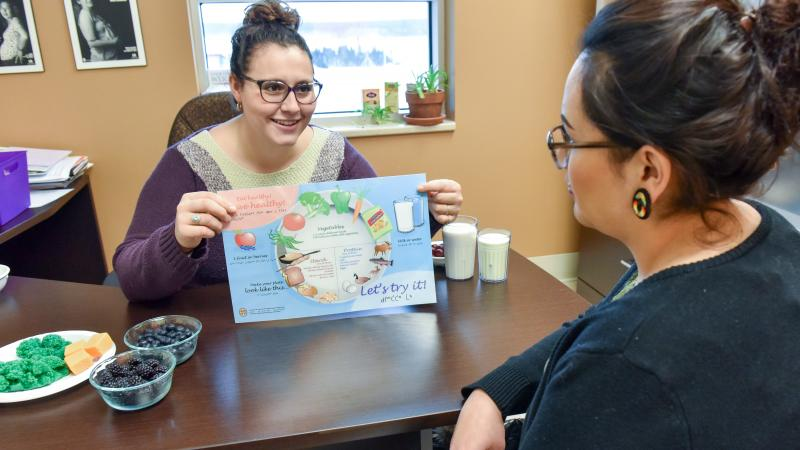 Nutritionist showing client Cree healthy placemat