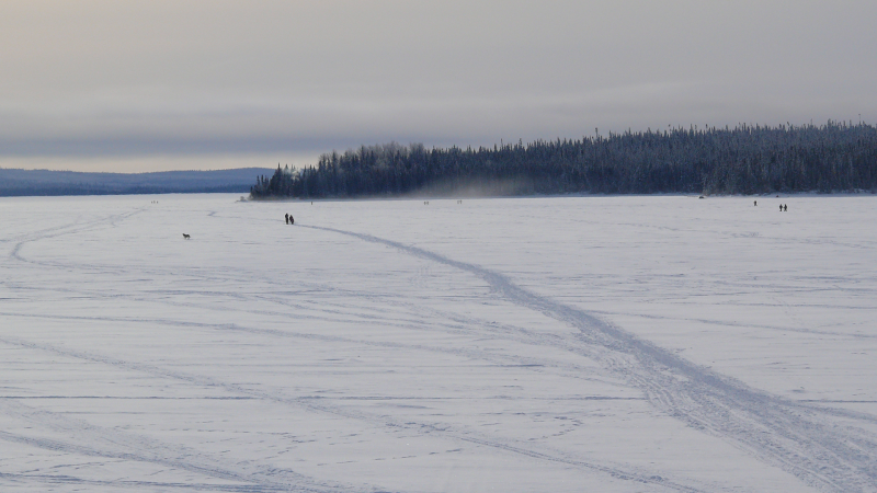 Tracks across frozen lake as people walk to be winter active